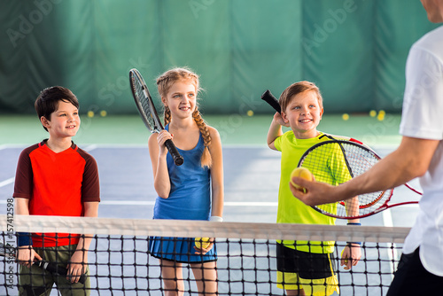 Leinwanddruck Bild Joyful pupils learning to play tennis