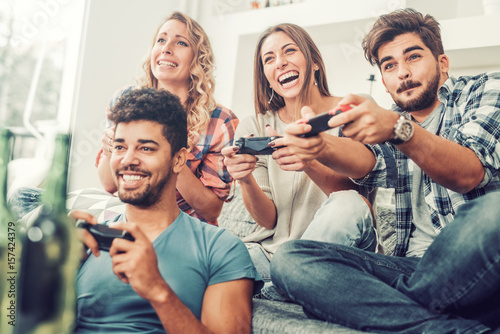 Young friends playing video games Poster