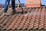 Washing the roof with a high pressure water washer. - 157450384