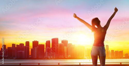 Jogging, Fitness And Success - Girl With Arms Raised And Cityscape At Sunset - 157467171