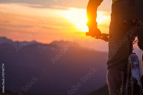Sylwetka męski mountainbiker przy zmierzchem w górach