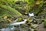 Górski wodospad w leśnej scenerii.