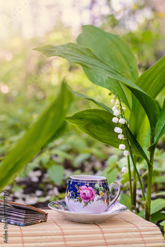 Aluminium Lelietjes van dalen A small Cup of tea next to the flowers of lilies of the valley