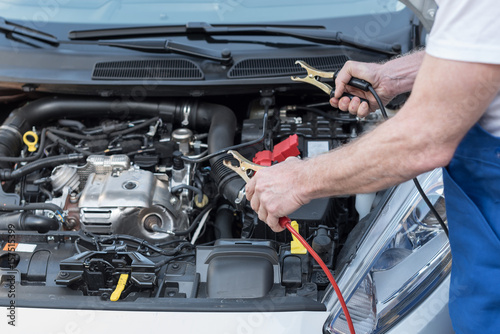 Car mechanic using car battery jumper cable Poster