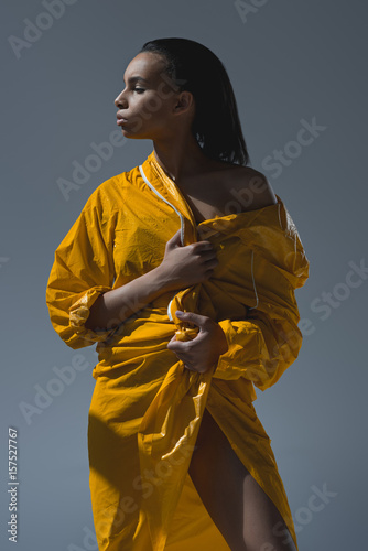 Gorgeous young african american woman holding yellow raincoat and looking away