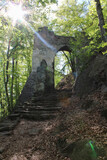 Stone gate in forest with strong light. Czech landscape