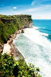 Pura Luhur Uluwatu temple, Bali, Indonesia. Amazing landscape - cliff with blue sky and sea. Vertical photo.