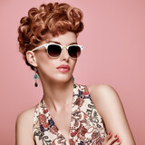 Fashion Portrait Model in Sexy Dress. Stylish Mohawk hairstyle,fashion Makeup.Beauty woman in Trendy Sunglasses,Glamour Redhead,fashion pose.Playful Girl,Luxury summer Accessories.Summer Floral Outfit