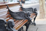 Wooden bench with figures of mythical heroes. London, UK.