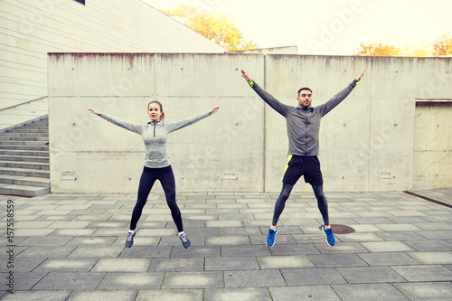 Póster happy man and woman jumping outdoors