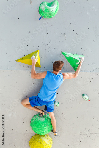 Poster Sports Man professional climber on artificial climbing wall in bouldering gym