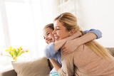 happy smiling family hugging on sofa at home - 157568354