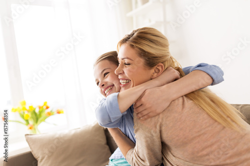 happy smiling family hugging on sofa at home