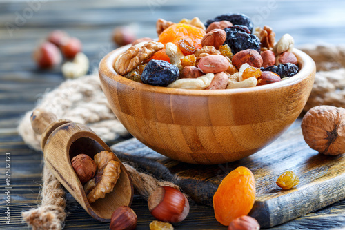 obraz lub plakat Wooden bowl with nuts and dried fruits.