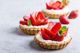 Strawberry vanilla cream cheese tarts over light gray table