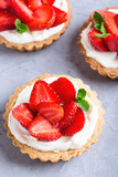 Strawberry vanilla cream cheese tarts over light gray table