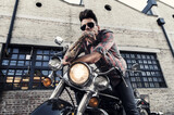 Tattooed cool young man with sunglasses sitting on vintage motorcycle   - 157601370