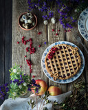 pie with berry filling on a white and blue plate with purple flowers, red currant, green leavesm quail eggsm fresh apples on a wooden table