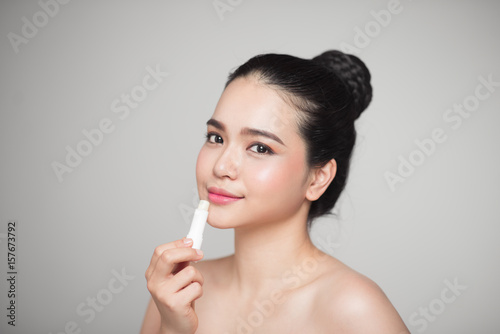 Asian woman applying hygienic lip balm over grey background Poster