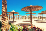 Chaise lounges and parasols on the beach against the blue sky and sea. Egypt, Hurghada - 157685733