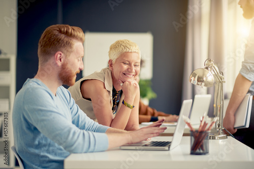 Caucasian businesswoman giving advice to her colleague while standing in modern office