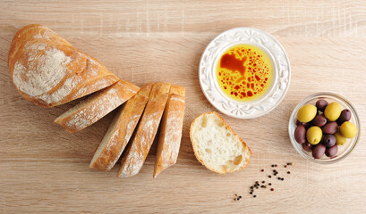 fresh bread, cut into slices with olives and olive oil with balsamic vinegar in a bowl