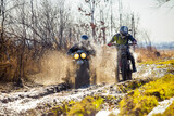 Fototapety Rally motorbike rider is ahead of another on a dirt road