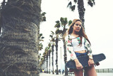 Portrait of young hipster girl holding skateboard while she standing on the lane lined with beautiful palm trees, cool trendy woman posing with her long board during recreation promenade in summer