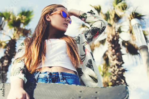 In de dag Barcelona View from below of trendy hipster girl in sunglasses holding her penny board against tropical sky background with copy space area, young stylish skateboarder woman relaxing after riding in summer day