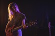 Confident female guitarist performing in concert