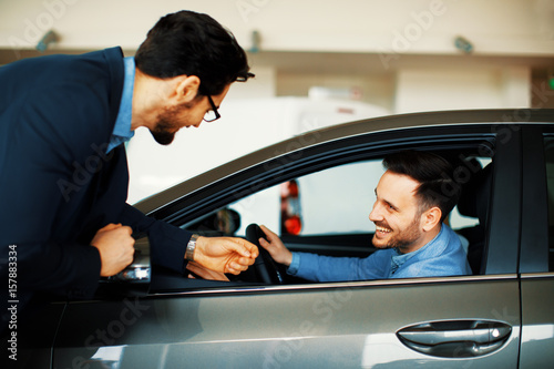 Young man choosing new car for buying in dealership shop
