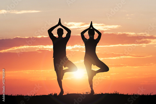 Silhouette Of Couple Doing Yoga Poster