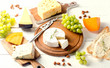 Different kinds of cheeses on  white wooden board