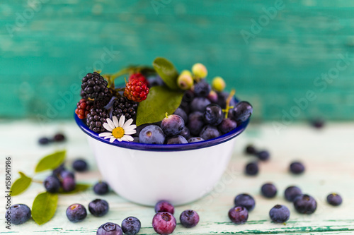 Tasty and fresh forest berries on wooden table.