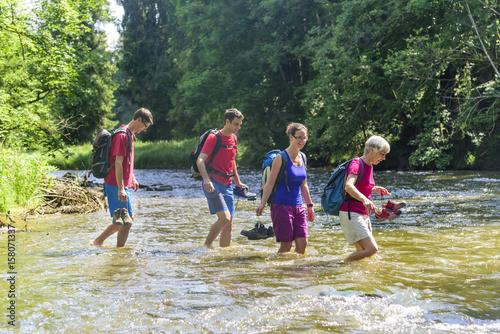 Wanderer durchqueren einen Fluss  an einer seichten Stelle Poster