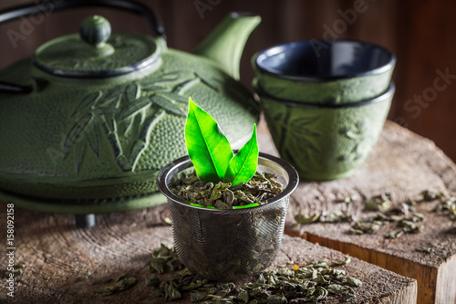 Aromatic green tea with iron teapot and cup