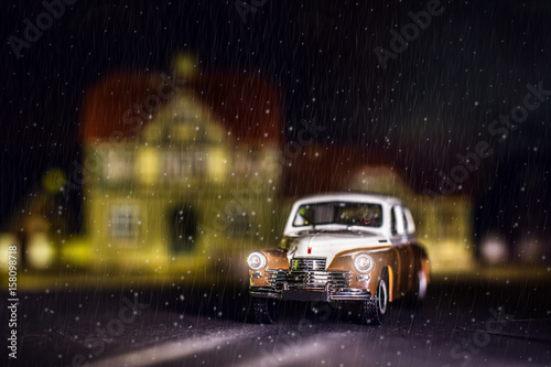 Photo of a miniature car GAZ-M20. Retro car rides through the city on a winter night. Snowing. Children's toy. Creative picture.