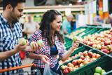 Fototapeta Man shopping in supermarket while pushing cart