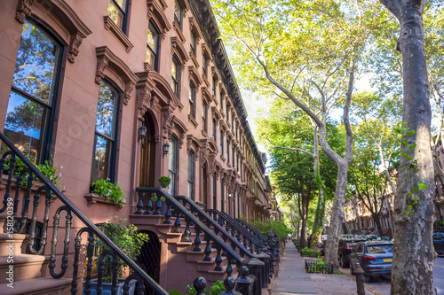 Foto Murales Scenic view of a classic Brooklyn brownstone block with a long facade and ornate stoop balustrades on a summer day in New York City