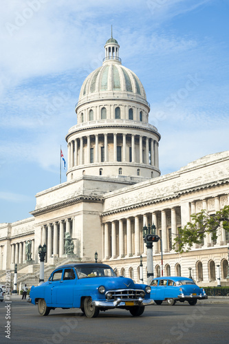 Aluminium Havana Brightly colored classic American cars serving as taxis pass on the main street in front of the Capitolio building in Central Havana, Cuba