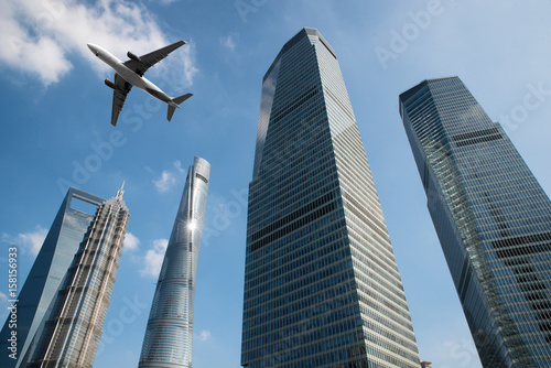Shanghai skyscrapers buildings and a plane flying overhead at in Shanghai luajiazui finance and business district in morning at Shanghai, China Poster