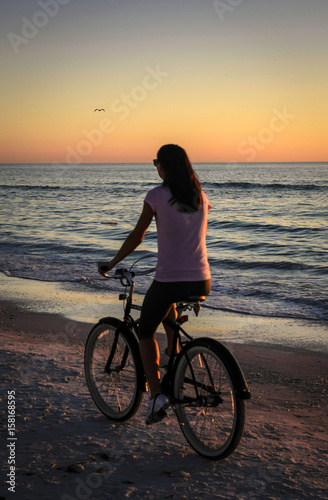 Young woman rides her bicycle along the Siesta Key beach in Florida at sunset Poster