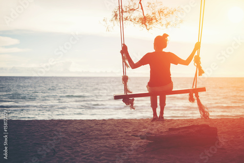 Young woman sitting on a swing at the beach. Poster