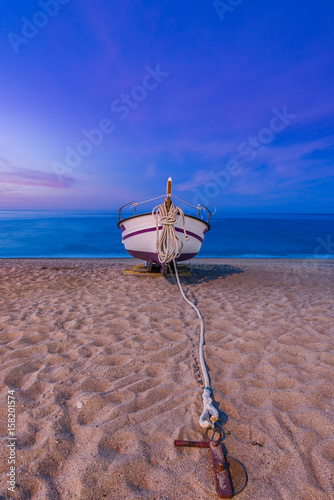 Papiers peints Bleu fonce Old wooden fishing boat on beach at sunrise