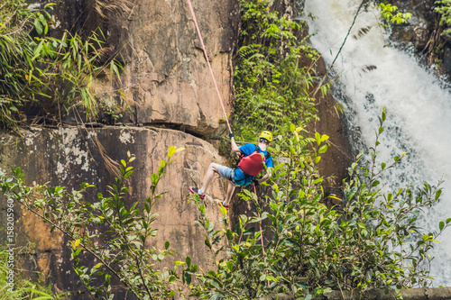 Poster Climber in the background of beautiful cascading Datanla waterfall In the mounta