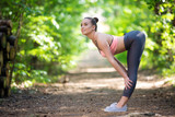 Beautiful slim woman exercising in the forest