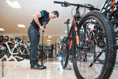 Deurstickers Male mechanic is pumping the wheels of bicycle