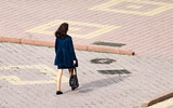 The girl is walking along paving stones
