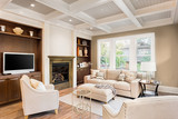 Beautiful living room with fireplace and hardwood floors in new luxury home. Coffered ceiling adds elegant touch. Built-in shelving compliments fireplace and surround.