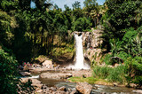 Tegenungan Waterfall. Beautiful powerful waterfall in the midst of a dense rainforest or jungle. Bali Indonesia.